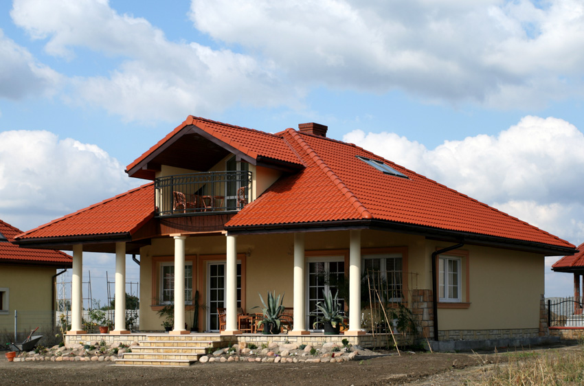 Low pitched red roof two storey house