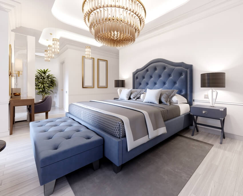 Luxurious bedroom suite in a contemporary style with a blue bed and white walls an armchair with footrest and dressing table with mirror