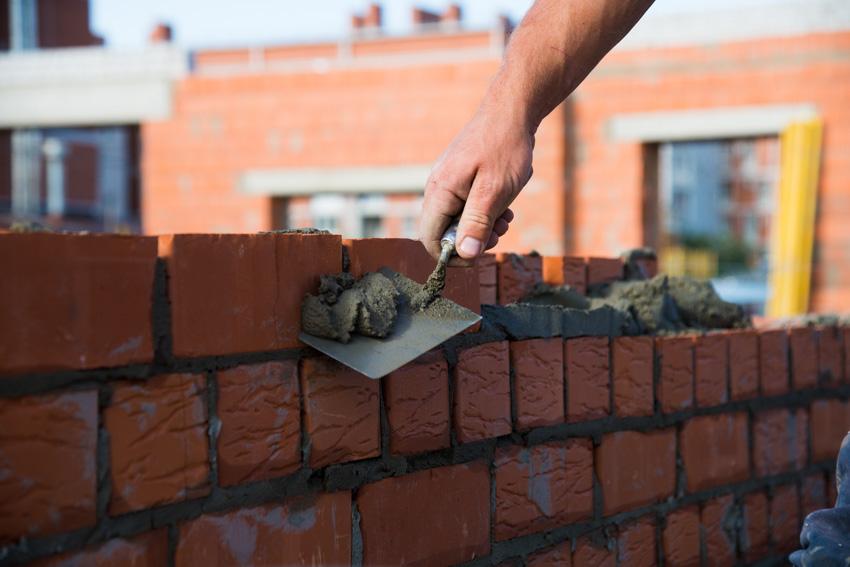 Man laying down red bricks