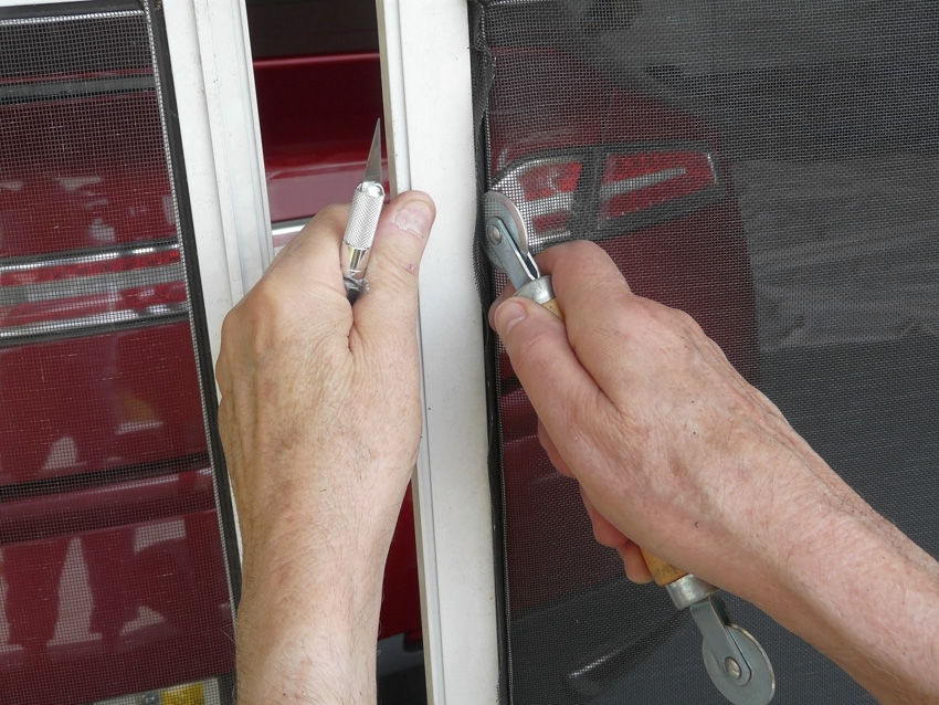 Man working on garage privacy screen red car
