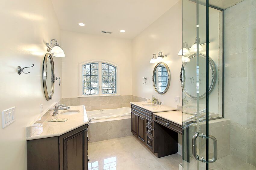 Master bathroom with glass shower mirrors bathtub and dark cabinets