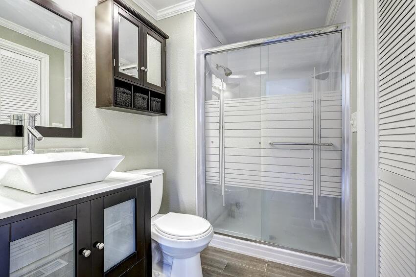 Modern bathroom interior with glass door, shower waterproof bathroom paint, brown vanity cabinet with white vessel sink and mirror