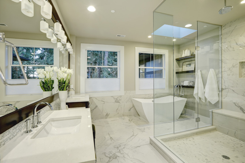 Modern bathroom with marble like porcelain tiles glass shower mirror sink windows lighting
