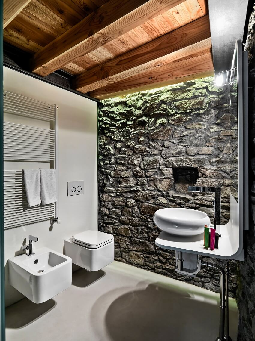 Modern bathroom with stone wall, wooden ceiling and resin-made floor