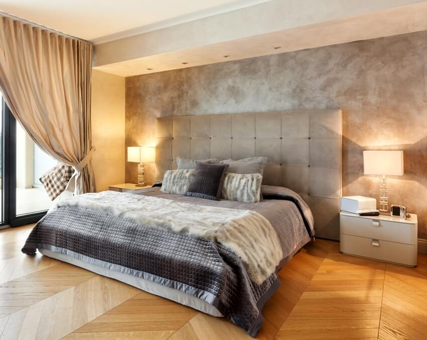 Modern bedroom with wooden floors a comfortable bed curtains and bedside lamp on table