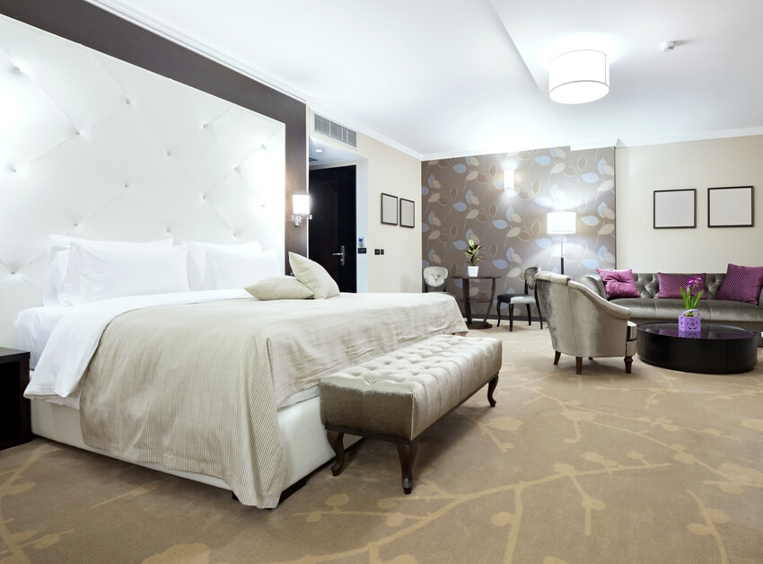 A modern master suite with carpet floors and gorgeous furniture