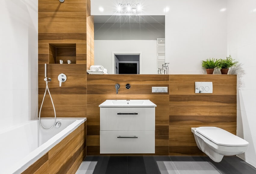 Modern wooden bathroom with PVC wall panels, bathtub, mirror, toilet, cabinet and sink
