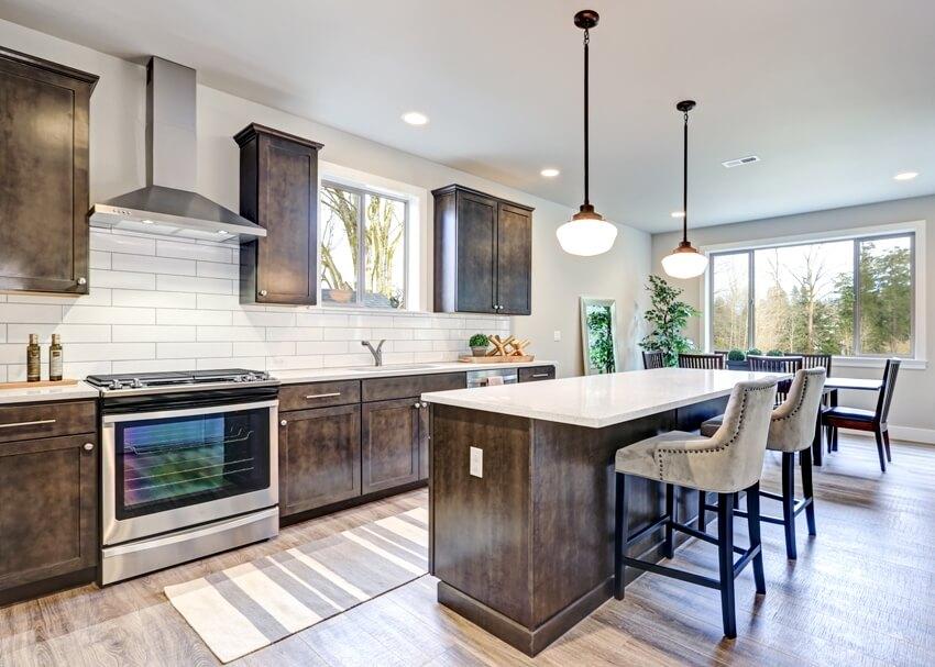New kitchen boasts dark wood cabinets white backsplash subway tile and over sized island with white and grey quartz counter