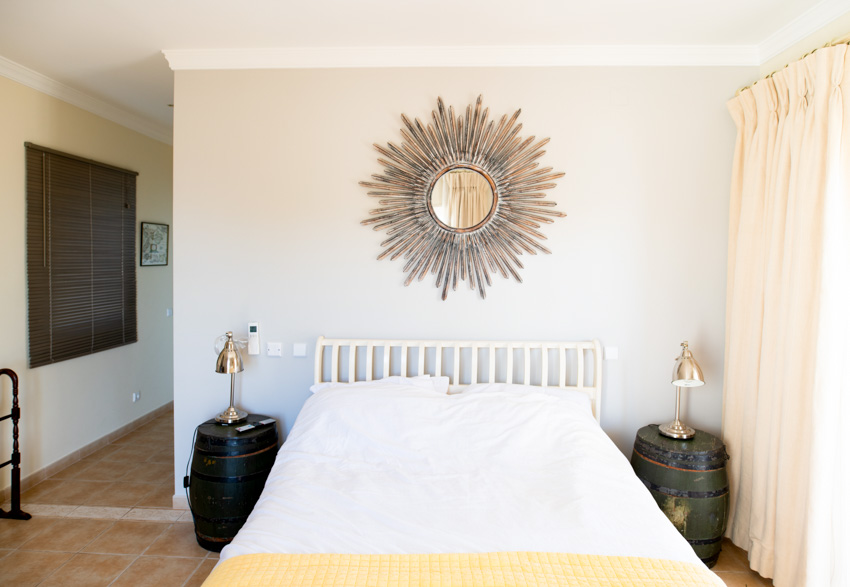 Ornate mirror decor hanging above white bed