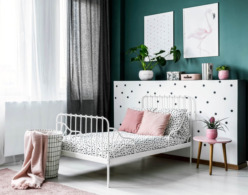 Pink flower on table next to white bed with foot railings in bright bedroom interior with posters on green wall