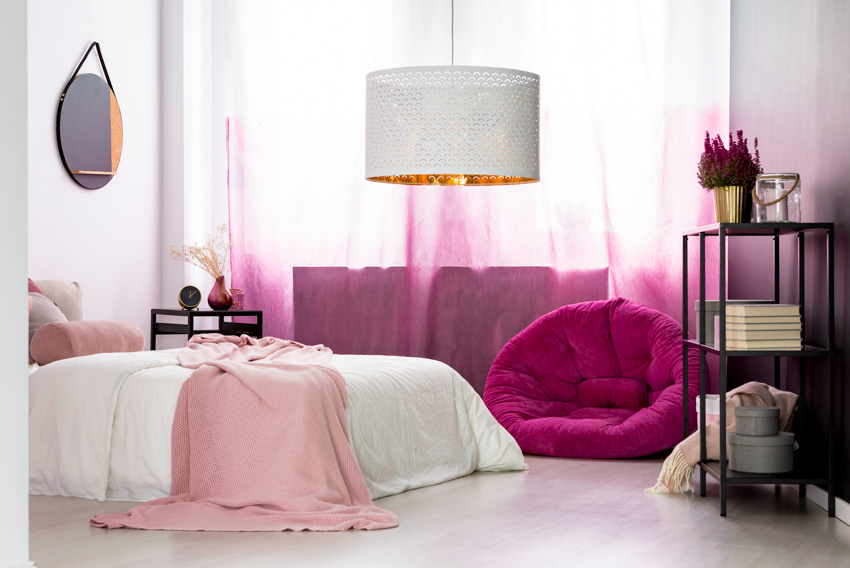 Pink themed room with mirror above bed