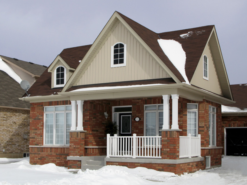 Pitched roof snow white and brick house exterior