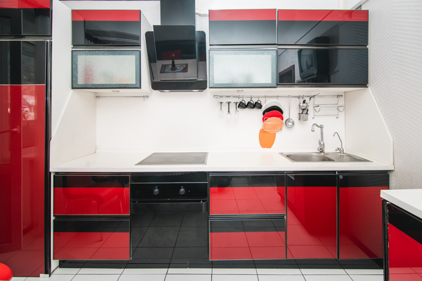 Red kitchen cabinets white tile flooring black oven and hood