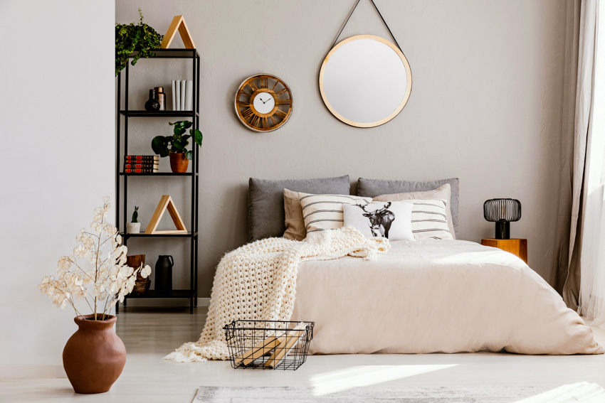 Round mirror hanging from wall shelf bedroom