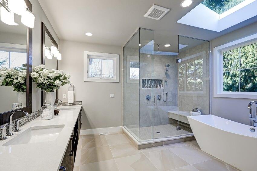 Spacious bathroom in gray tones with heated floors, freestanding tub, walk in shower, double sink vanity and skylights