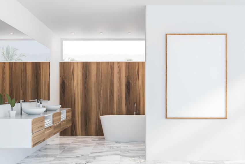 Spacious bathroom with porcelain tiles that look like marble mirror sink bathtub