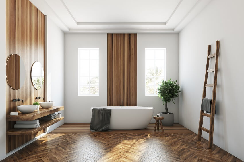 White and wooden bathroom interior with a vinyl wallpaper, wooden floor, a white tub and two narrow windows