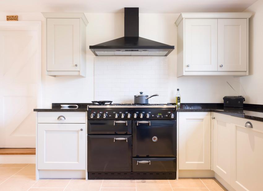 White kitchen cabinets black oven hood countertop stove
