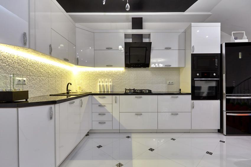 White kitchen cabinets tile flooring black oven hood countertop refrigerator