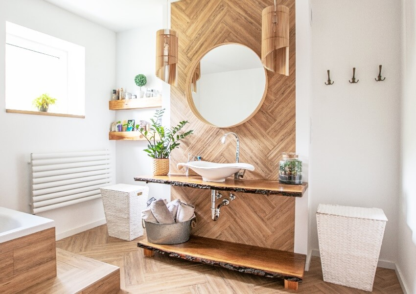 White sink on wood counter with a hanging round mirror bathroom interior