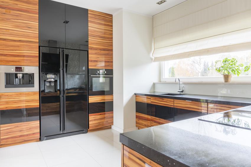 Wood cabinets black countertop refrigerator glass kitchen window