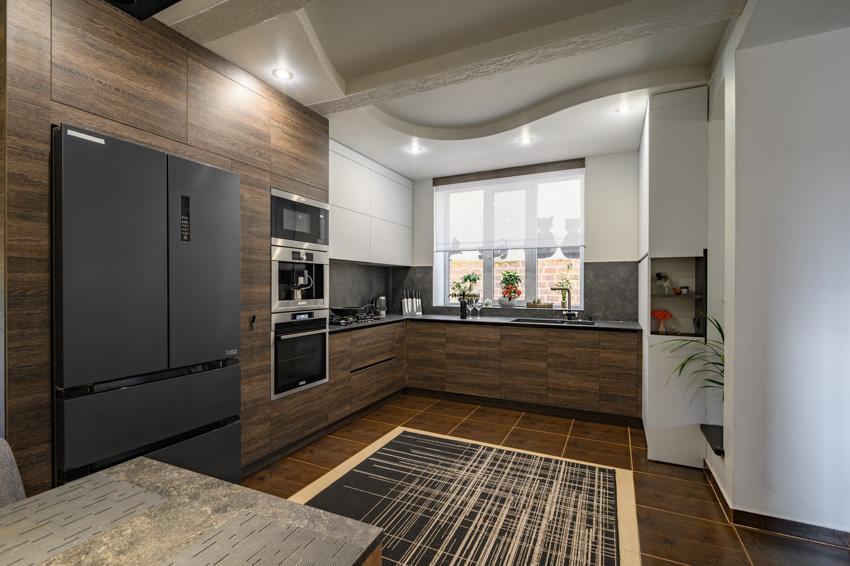 Wood cabinets drawers black refrigerator countertop sink window recessed lighting