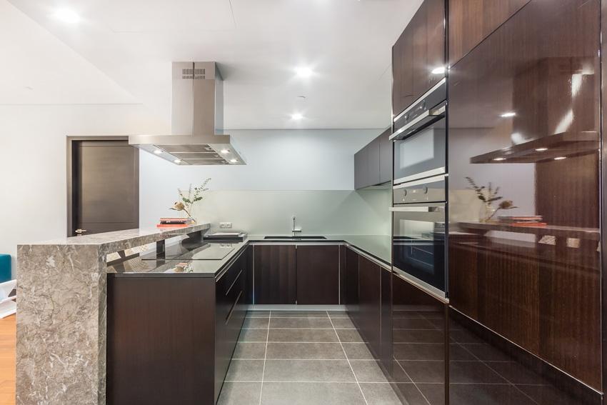 Wood cabinets hoot black oven tiled floor